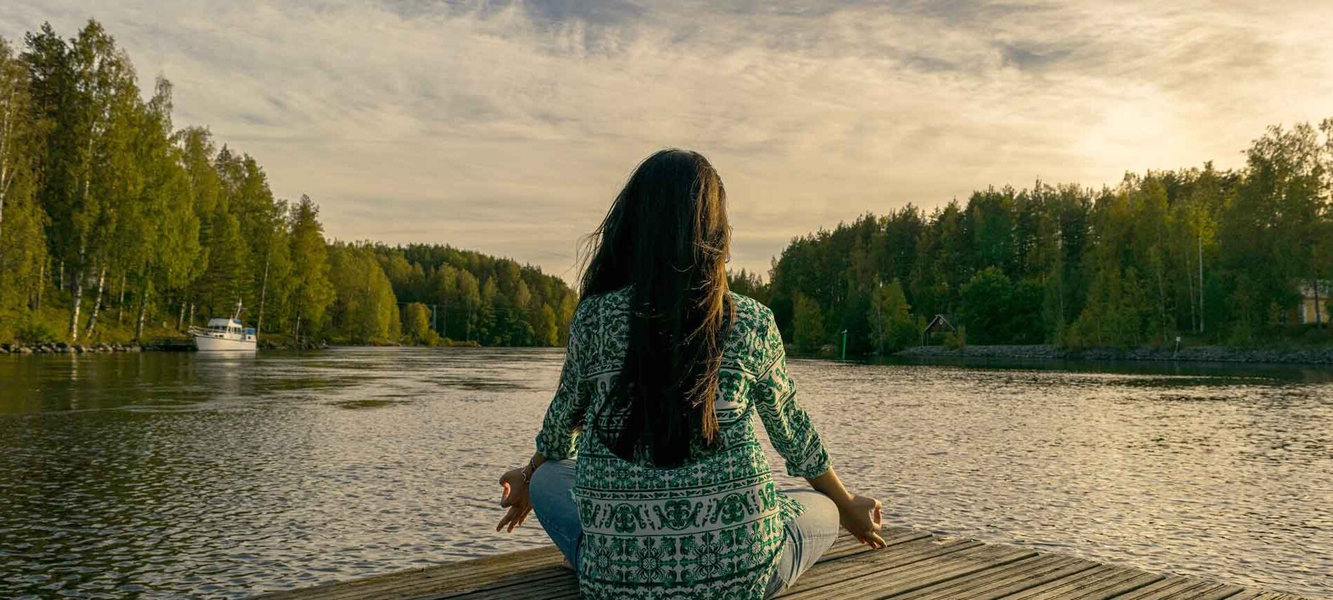 A woman sitting on a lake dock practicing meditation